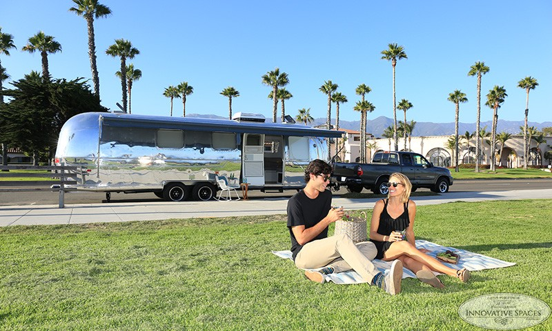 A couple sitting near a trailer that used services from an Airstream renovation company